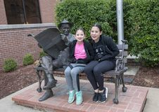 Sisters posing with bronze of Will Rogers on a bench, Claremore, Oklahoma. Pictured are nine and thirteen year old Amerasian sisters posing with a sculpture of Royalty Free Stock Images