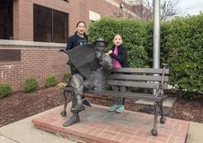Sisters posing with bronze of Will Rogers on a bench, Claremore, Oklahoma. Pictured are nine and thirteen year old Amerasian sisters posing with a sculpture of Royalty Free Stock Image