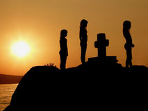 Sisters in prayer on sunset. Sisters in prayer on the stone with cross Stock Photo