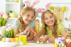 Portrait of sisters preparing for Easter in the kitchen royalty free stock photography