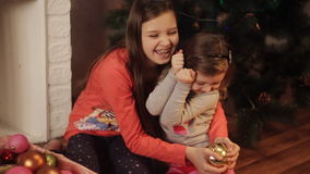 Sisters are preparing for the new year, choose Christmas decorations. Two little sisters decorating Christmas tree with fir-cone. New year preparation. Happy stock video