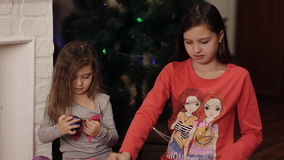 Sisters are preparing for the new year, choose Christmas decorations. Two little sisters decorating Christmas tree with fir-cone. New year preparation. Happy stock video footage
