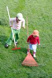 Sisters raking up the cut grass. Two little girls raking up the grass in the yard Royalty Free Stock Photography