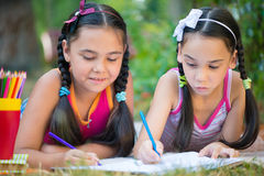Sisters reading book in summer park Royalty Free Stock Photography