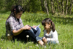 Sisters reading book together. Teenage girl reads a story to little sister Royalty Free Stock Photos