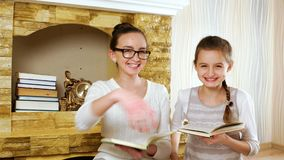 Sisters reading textbooks near fireplace at home, girls smiling and hugging, wearing glasses stock video footage