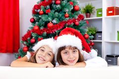 Sisters in red santa hat Stock Photos