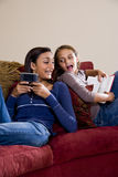 Sisters relaxing together at home on sofa Royalty Free Stock Photography
