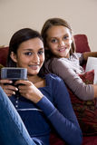 Sisters relaxing together at home on sofa Stock Photos