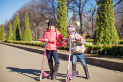 sisters ride scooters on a warm sunny spring day Stock Photos