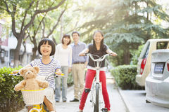 Sisters Ride Their Bicycles While Parents Watch Stock Photo