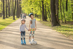 Sisters roller blading together, holding hands Stock Photos