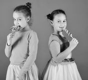 Sisters with round and long shaped lollipops. Children with happy faces pose with candies on green background. Treatment and sweets concept. Girls eat big royalty free stock image
