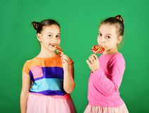 Sisters with round, long shaped lollipops. Girls with happy faces. Sisters with round and long shaped lollipops. Girls with happy faces pose with candies on royalty free stock images