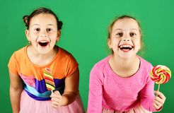 Sisters with round and long shaped lollipops. Girls eat big colorful sweet caramels. Treatment and sweets concept. Children with excited faces pose with stock photography