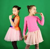 Sisters with round and long shaped lollipops. Treatment and sweets. Concept. Girls eat big colorful sweet caramels. Children with busy faces pose with candies royalty free stock image
