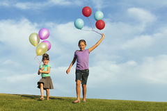 Sisters Running With Balloons Stock Photo
