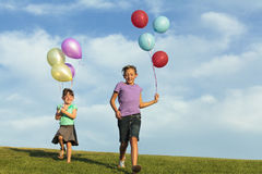 Sisters Running With Balloons Stock Image