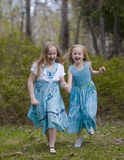 Sisters Running in Spring Dresses Stock Images