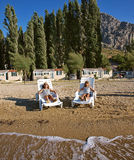 Sisters on sand beach lying on deck chairs Stock Photo