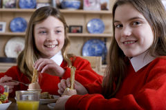 Sisters in school uniform having breakfast Royalty Free Stock Images