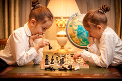 Sisters in school uniform playing chess Royalty Free Stock Image
