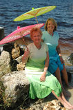 Sisters by the sea. Two mature women with colorful parasols by the ocean stock image