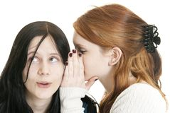 Sisters sharing secrets. A teenage Caucasian girl whispers a secret to her sister. Focus on face of dark haired girl Royalty Free Stock Photo