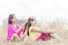 Sisters sit in country meadow braiding hair Stock Image