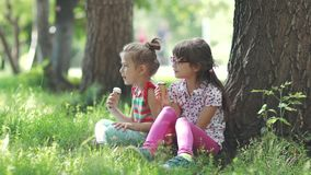 Sisters sit on the grass in the summer Park and eat ice cream. happy carefree childhood. Carefree children eat ice cream in summer Park. two little girls having stock video