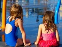 Sisters Sit at a Splash Pad Royalty Free Stock Photography