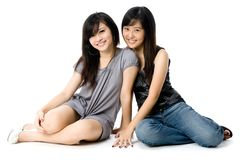 Sisters Sitting. Two young Asian women sitting together on white background stock image