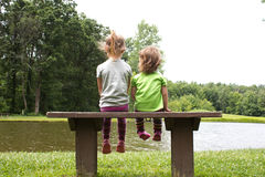 Sisters sitting on a bench Royalty Free Stock Images