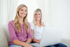 Sisters sitting on the couch looking at the camera as they hold Stock Photo