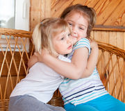Sisters sitting embracing each other. Two little sisters sitting embracing each other at home Royalty Free Stock Photo