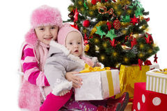 Sisters sitting with gifts under Christmas tree royalty free stock photos