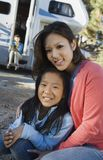 Sisters sitting outside RV in campground Stock Image