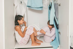 Sisters sitting and playing in wardrobe Stock Photos