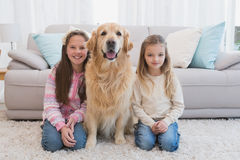 Sisters sitting on rug with golden retriever smiling at camera Stock Photos