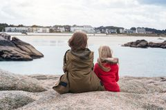 The sisters are sitting on the shore of the ocean. Sisters sitting near the sea the shore at  the Tregastel, Brittany. France royalty free stock photo
