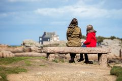 The sisters are sitting on the shore of the ocean Royalty Free Stock Images