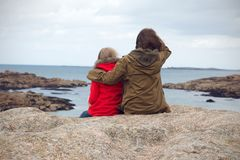 The sisters are sitting on the shore of the ocean. At  the Tregastel, Brittany. France royalty free stock photo