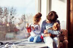 Sisters sitting on the windowsill with the dog. The concept of C. Hristmas stock photos