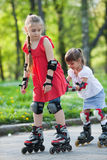 Sisters skating in park Royalty Free Stock Images