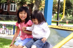 Sisters on a slide. Sisters having fun on a playground Stock Image