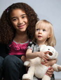 Sisters smiling and holding toy bear Stock Photos