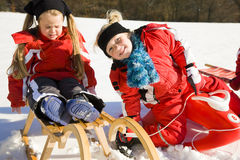 Sisters in snow on toboggan royalty free stock photos