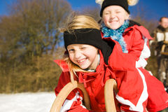 Sisters in snow on toboggan royalty free stock image