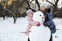 Sisters with snowman Royalty Free Stock Photos
