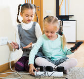 Sisters with socket extender Royalty Free Stock Photo